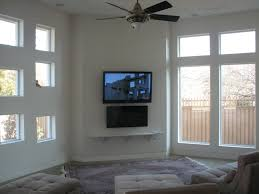 black electric fireplace under wall mounted tv combined with large white stained wooden frame glass window