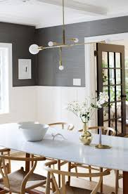 dark grey wallpaper above white panelling mid century table and light fixture wishbone chairs