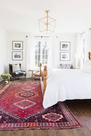 Simple with bright rug! bedroom with white walls, white bedding, antique  rug, seating