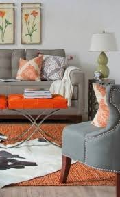 orange living room chairs. vibrant orange accent pieces on a grey palette. living room chairs 6