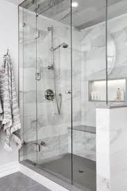 Polished nickel towel hooks are mounted beside a seamless glass steam shower  featuring a lighted niche framed by gray and white marble wall tiles and ...