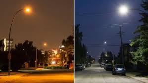 the orange glow of calgary s old high pressure sodium bulbs is seen at left and the cooler white light of the new led fixtures is seen at right