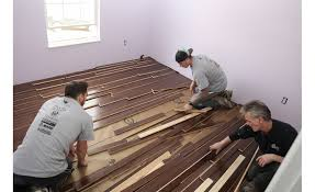 volunteers installing sheoga hardwood flooring in a bedroom at army veteran chris sanna s home