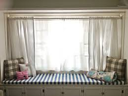 um size window with white window curtains a window bench with storage and cozy seating