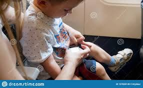 closeup image of pa helping child fastening airplane seat belts concept of safety in aircraft