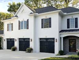painting a garage door with a roller a large white brick house has three garages across
