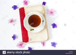 old book with tea or coffee with flowers on white background