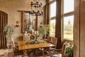 elegant tuscan dining room with wrought iron chandelier over square table and decorated with houseplants and