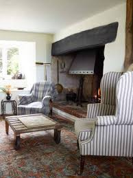 the main living room in this wiltshire farmhouse has an inglenook fireplace with fifteenth century firedogs and an eighteenth century fire back added by