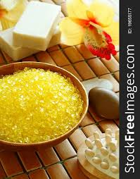 spa composition of yellow bath salt in wooden bowl