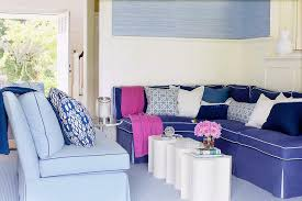 chic living room with blue velvet sectional sofa with white piping accented with hot pink throw blanket white and blue geometric pillows blue pillow and