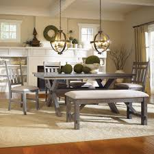 grey wooden design of dining room table with chairs and bench white rug and white fireplace