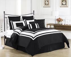 good looking black and white comforter on wooden bed frame which