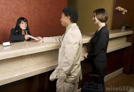 a hotel front desk receptionist checks in guests