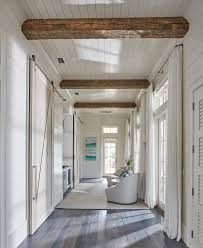 floor to ceiling shiplap paneling with reclained wood beam this hallway boasts rustic wood beam