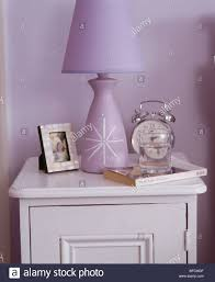 Mauve Bedroom Close Up Of Alarm Clock And Mauve Lamp On White Bedside Cabinet In