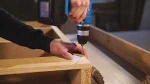 making industrial furniture. Worker Is Making Holes In A Timber Detail Of Piece Furniture For Assembling. He Industrial