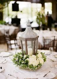 wood lantern and white flowers wedding centerpiece