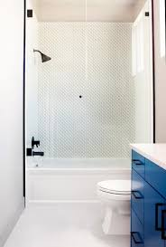 a white drop in bathtub is fitted with a seamless glass enclosure and an oil rubbed bronze shower kit mounted to white shower tiles accented with white