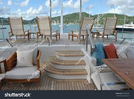 super yacht aft deck with lounge chairs and view of antigua harbor caribbean