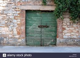 old green wooden garage doors with heavy metal lock and brick frame inside traditional stone wall