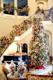 Amazing luxurious Christmas decoration with elegant high Christmas tree  filled with lots of beautiful ornaments and stunning staircase handrails  decor.
