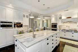 transitional style kitchen with classic white cabinets oak hardwood flooring and contemporary calacatta marble countertops