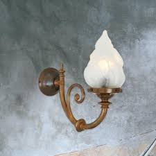 traditional one light antique brass wall sconce fitting flame shaped glass lamp shade