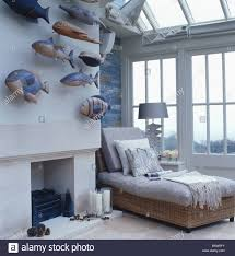 Collection Of Painted Wooden Fish Above Fireplace In Loft Conversion Bedroom  With Gray Day Bed In Front Of Large Window