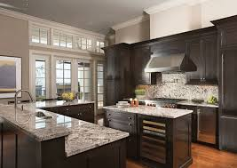 beautiful dark wood cabinet kitchen with light color granite counters and stainless fixtures