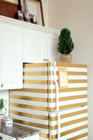 white fridge in kitchen. striped fridge in golden color, white kitchen cabinets