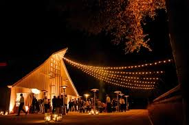 outdoor cocktail hour with string lights in front of barn barn wedding lights