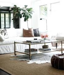 a black and white cowhide rug is layered atop a bound sisal rug in this stunning white cowhide rug faux black