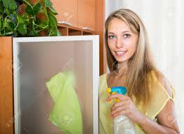 dusting furniture. Stock Photo - Young Smiling Woman Dusting Glass Of Furniture At Home