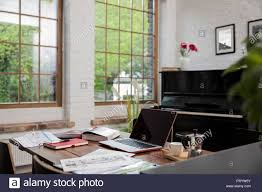 Loft home office Style Home Office With Piano In Background At Comfortable Loft Apartment Canadianartcom Home Office With Piano In Background At Comfortable Loft Apartment