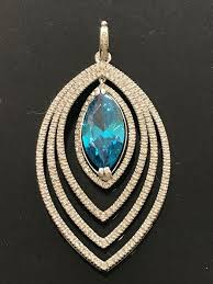 gold pendant decorated with a synthetic blue stone surrounded by 3 60 ct of top wesselton diamonds