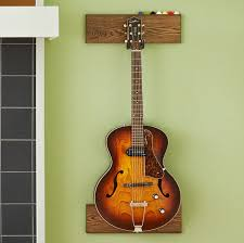 hang a guitar from the hook to determine the placement of the bottom board remove the guitar and mount the baseboard the same as the top board