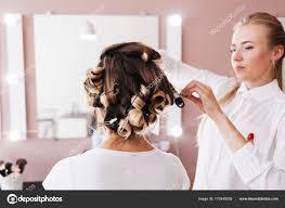 女性美容師のサロンで茶色の髪の女性に髪型を作る ストック写真