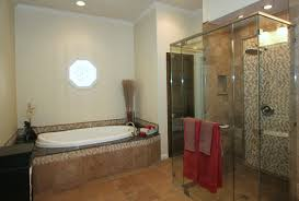 oval white bathtub and glass shower stalls connected by beige wall