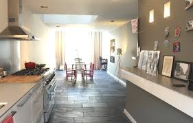slate kitchen tile flooring under light gray countertop and small pictures on kitchen shelf near