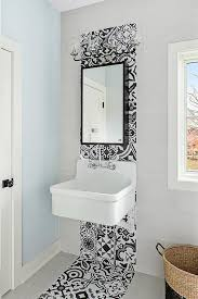 large gray grid bathroom wall tiles are accented with black and white cement tiles fixed behind a black framed medicine cabinet lit by a 4 light black