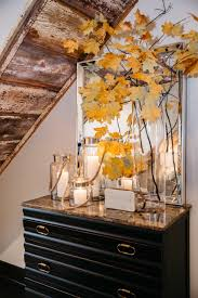 A tall vase with two branches from a maple tree growing in the homeowner's  woods finishes this vignette. Styling tip: always go with the biggest  mirror your ...