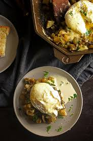 overhead photo of a plate of eggs benedict next to a cast iron skillet filled with