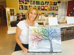 jeanne shirley owner of painting with a twist poses with the painting for saay s