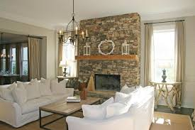 stone fireplace in white living room wall with white sofa