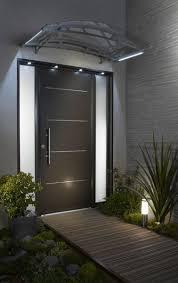 style déco design devant la porte d entrée noire de cette maison soulignée par une allée en bois et de la verdure judicieut illuminé par des lumières