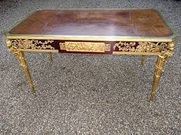 writing desk in gilt bronze with a leather top cherub heads on the corners france 19th