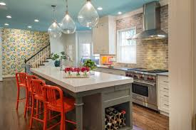 view in gallery kitchen with a blue ceiling and bright orange bar stools