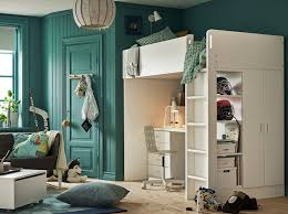 children s bedroom with turquoise walls and white loft bed with desk and drawers underneath