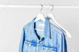 Light Gray Denim Jacket Blue Denim Jacket On White Wooden Coat Hanger On A Rod Against